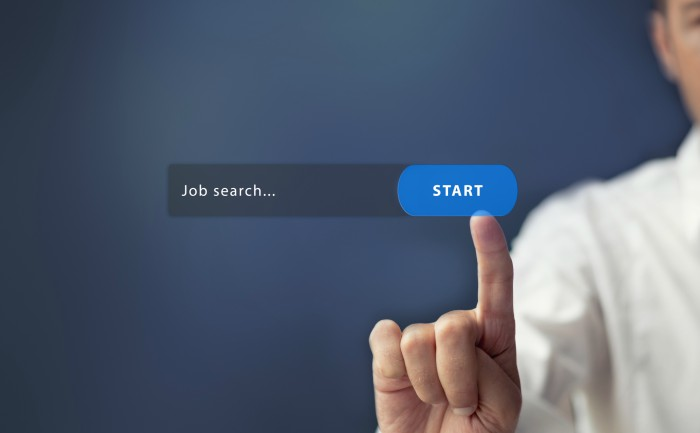 A job applicant clicking on an online job search bar.