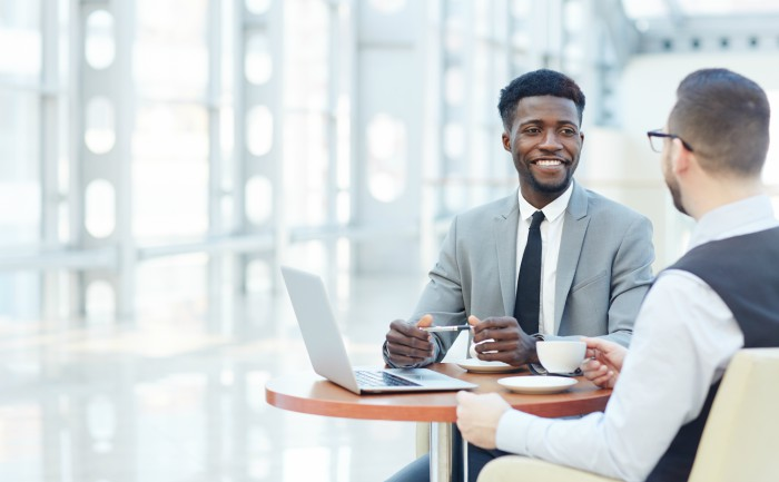 Two business professionals have a conversation over coffee