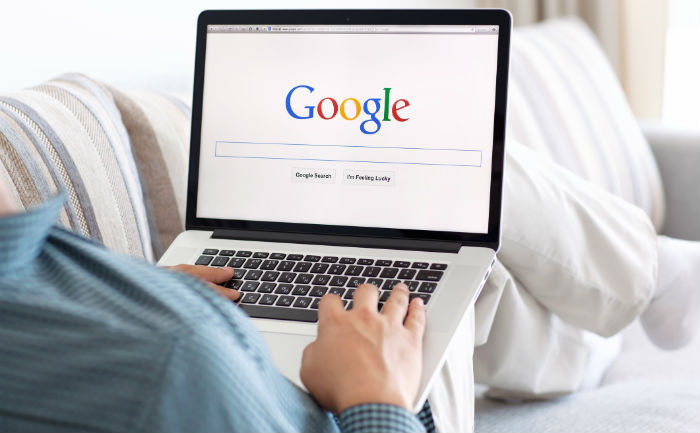 Person sitting on couch with laptop and looking at the Google browser before using Google Docs hacks.