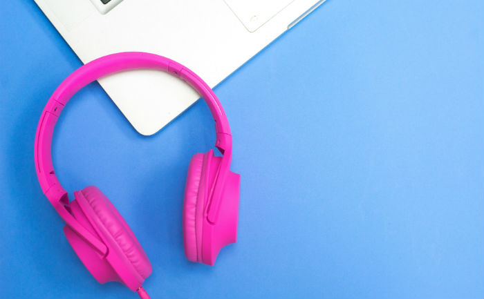 Bright pink headphones sitting on the edge of a laptop with a blue table underneath.