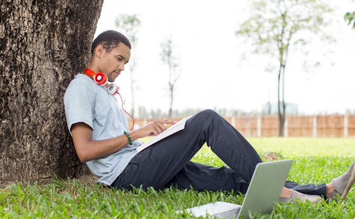 Young man sitting in the grass and leaning against a tree while learning how to improve study habits.