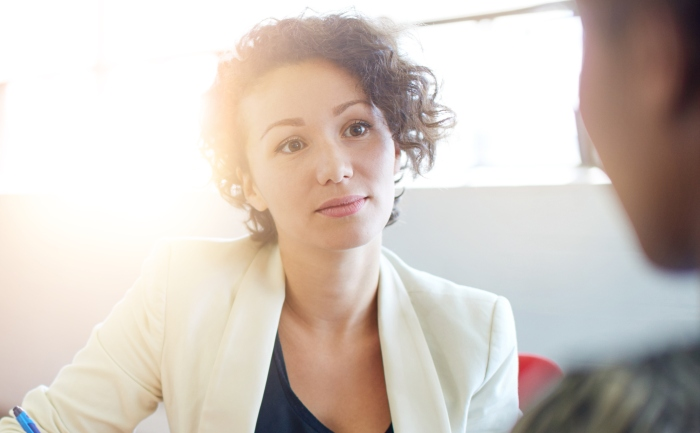 Business woman jotting down notes in an interview setting