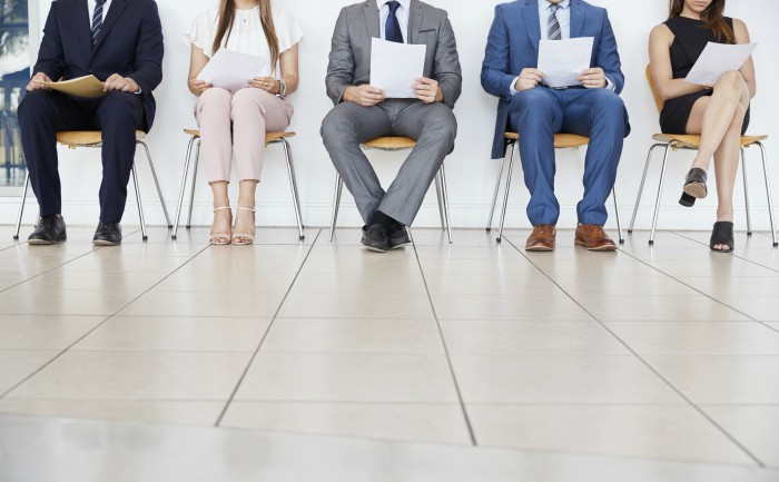 Job candidates sitting in a waiting room ahead of a job interview