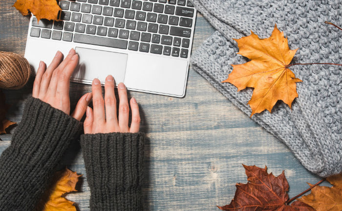 Person wearing a sweater and using silver laptop, surrounded by a gray blanket | How to be successful as an online student | UTEP Connect