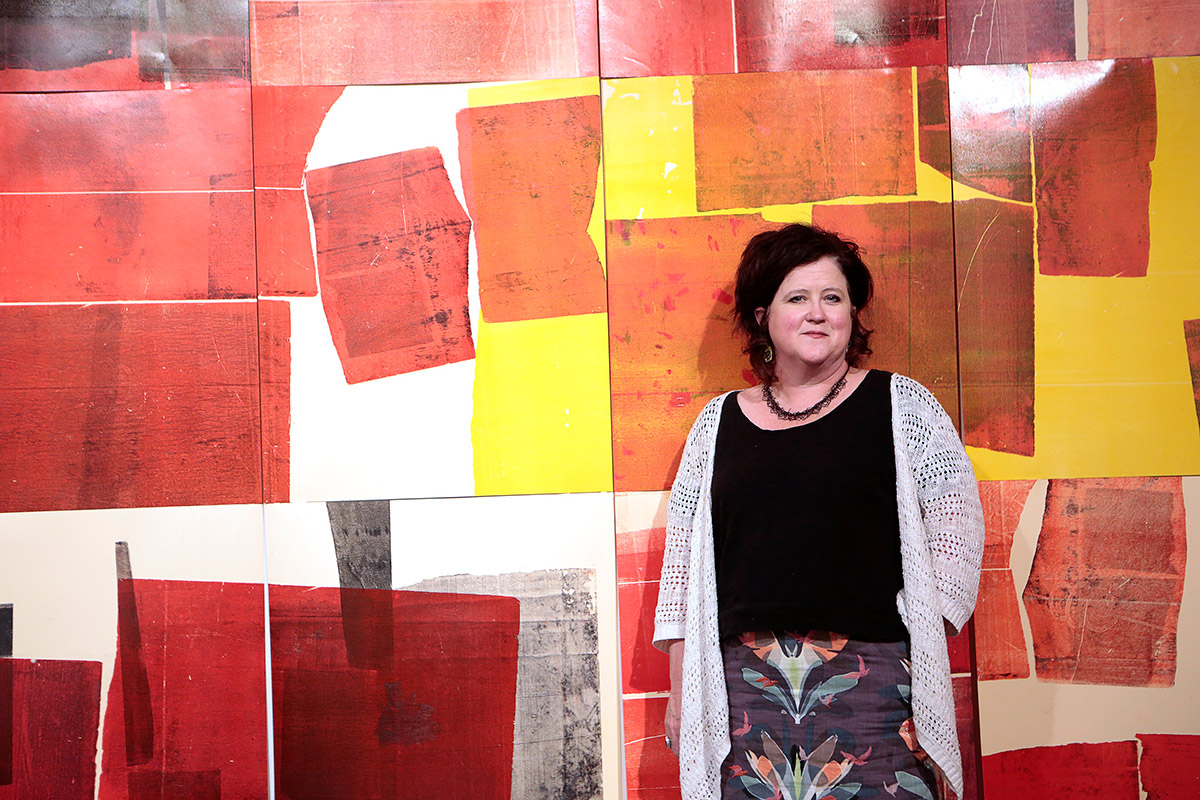 Kerry Doyle, director of the Stanlee and Gerald Rubin Center for the Visual Arts, stands in front of 'A Miscommunication With Conversatimalists' by Jason Lucero, which was voted Overall Best of Show at the 2018 Annual Juried UTEP Student Art Exhibition.  Photo: J.R. Hernandez / UTEP Communications