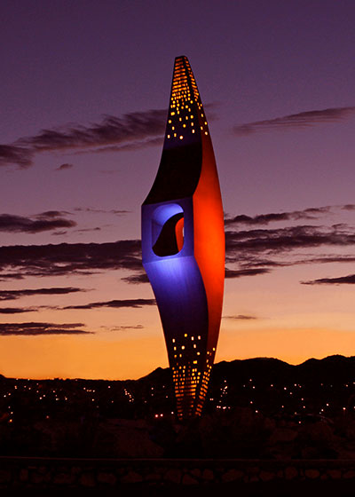 The University of Texas at El Paso will illuminate the 'Mining Minds' pickaxe sculpture at the campus' University Avenue roundabout in blue and orange Tuesday evening, April 16, 2019, to commemorate the establishment of the School of Mines, now UTEP.