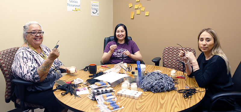 Faculty, staff and students from The University of Texas at El Paso, have volunteered their time to help the migrants who cross the border into El Paso from Mexico and countries in Central America. A group of volunteers including Yolanda Leyva, Ph.D., left, associate professor of history and director of UTEP's institute of Oral History, made shoelaces recently for refugees who must surrender their shoelaces and belts when they enter the custody of U.S. authorities. Photo by Laura Trejo / UTEP Communications